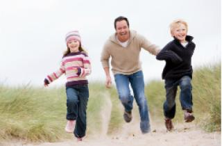Father & two children running on the beach