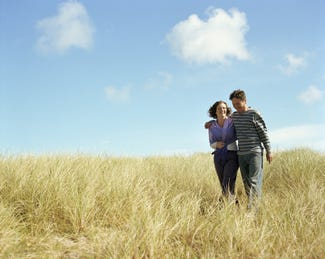 Couple walking through sand dunes