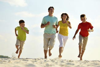 Family running on the beach in Summer