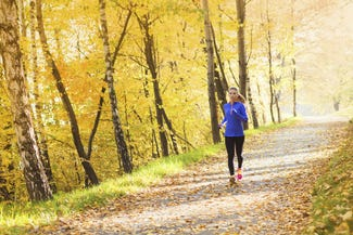 Girl running in a woodland area