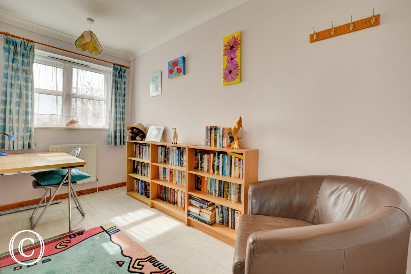 A small study/library with a desk sofa, and selection of books.