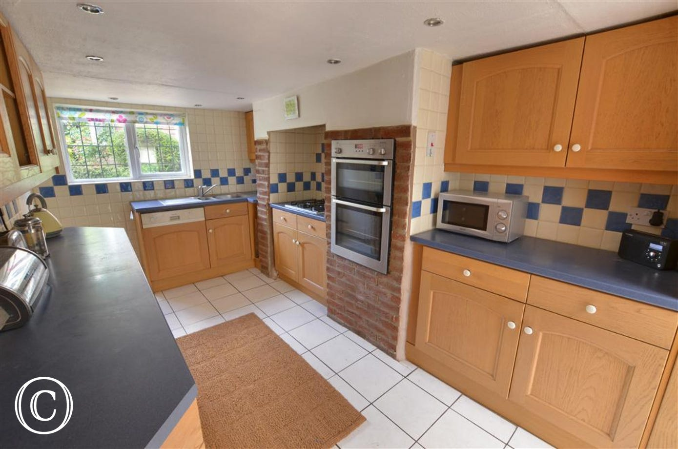 View of kitchen, showing integrated oven, gas hob under surrounds, sink with window above.