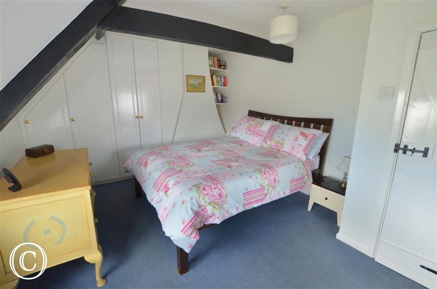 View of bedroom 1 with double bed dressed in pretty bedlinen, dressing table and built in cupboards under eaves.