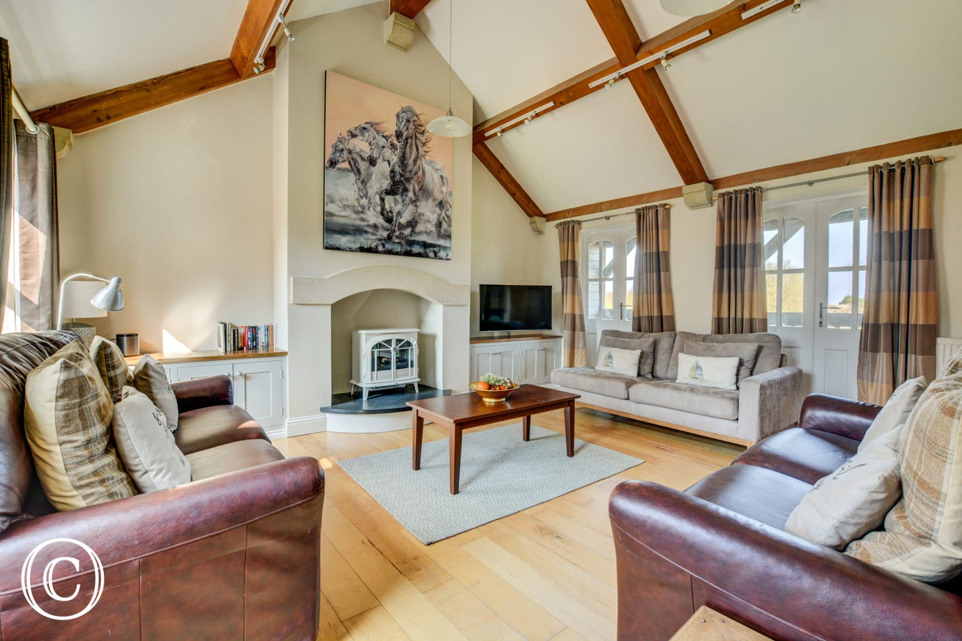 Spacious sitting room with a verandah to take full advantage of the uninterrupted views towards the sea and over Thornham marshes