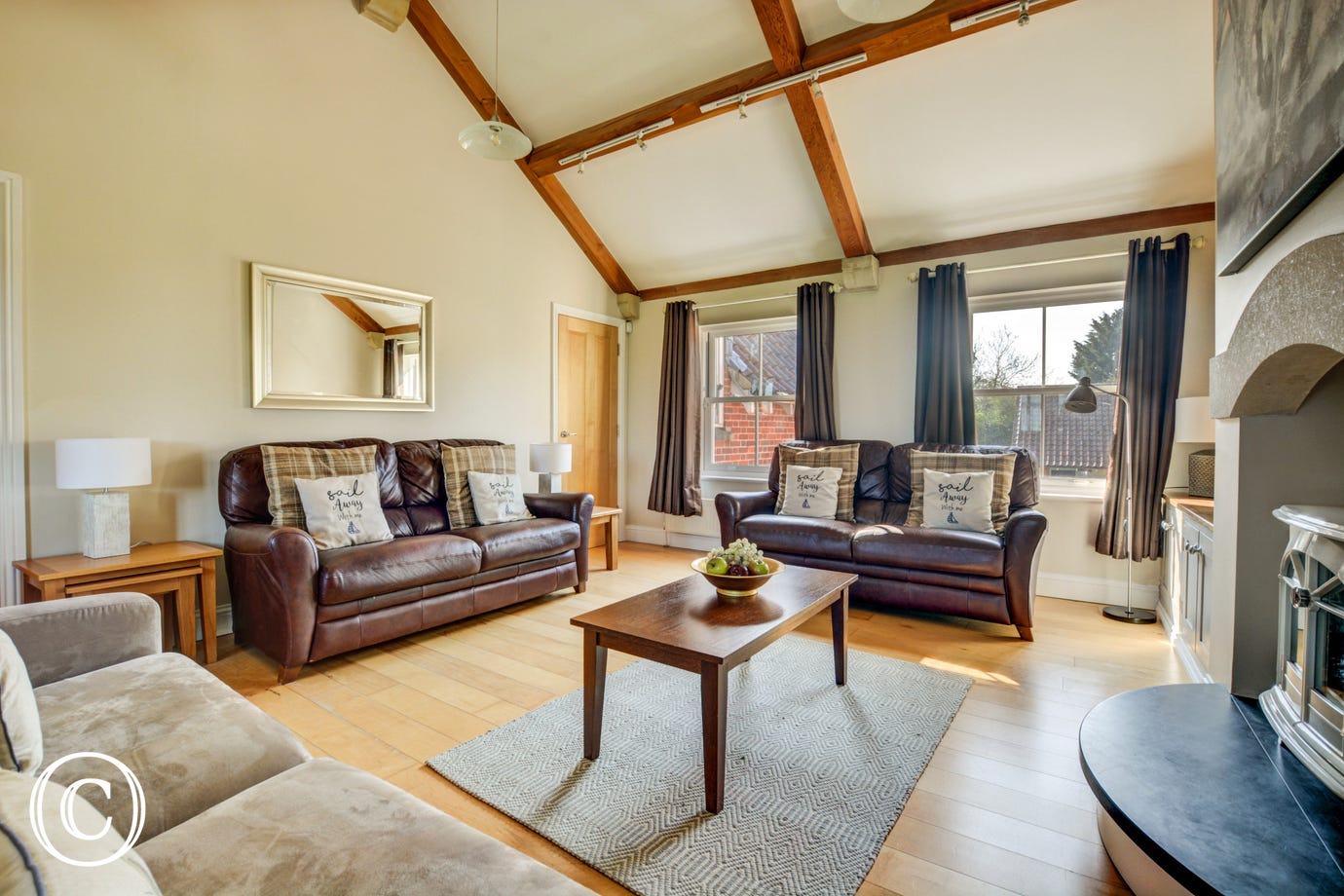Stylishly presented sitting room with comfortable seating - three large sofas, electric living flame fire and French doors to the balcony, super family room