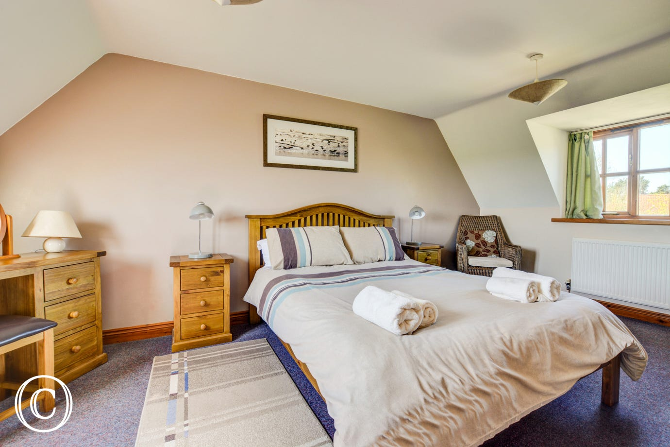 A comfortable and spacious double bedded room with television.
