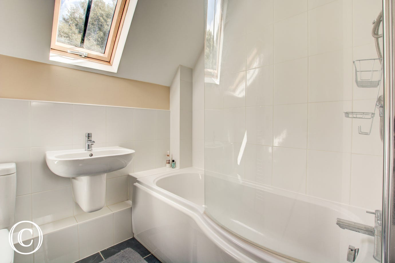 White bathroom suite with a bath, hand held shower, WC and wash hand basin