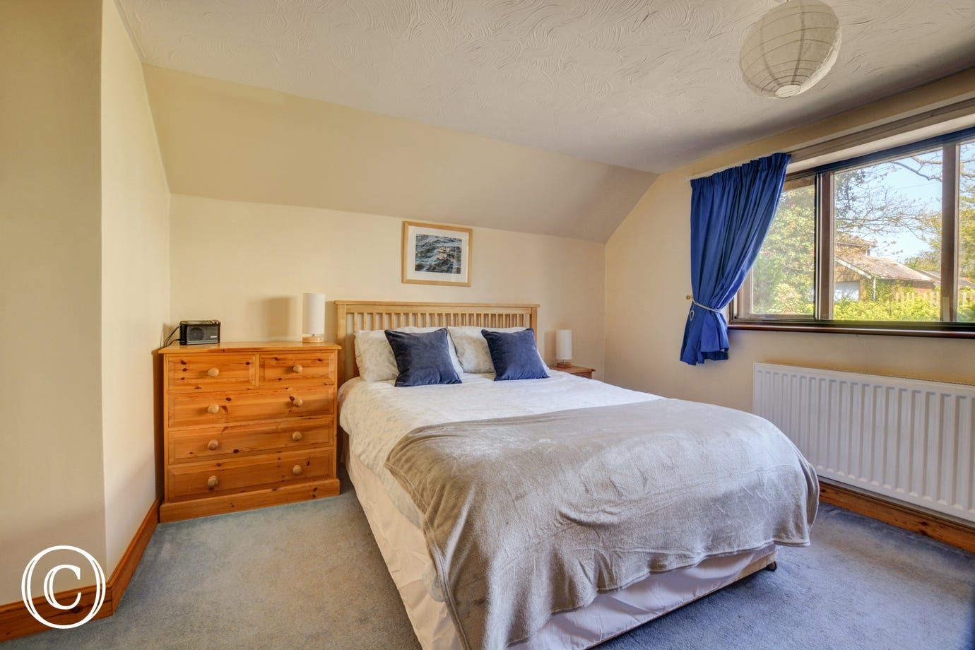 Light and airy double bedroom with a with a king-size bed and washbasin - please note there are two or three steps from hallway up to this bedroom