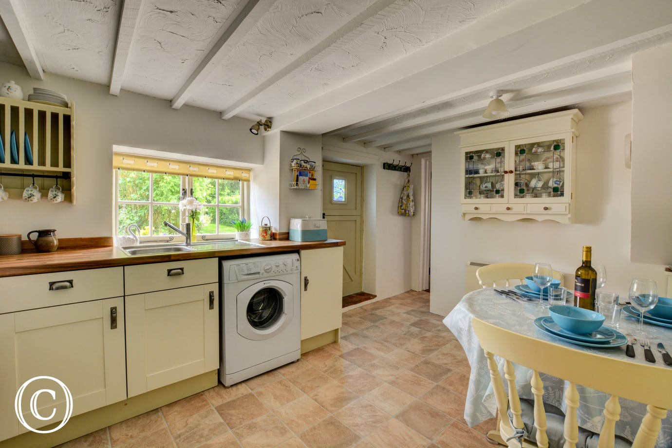 Kitchen with view of dining area and door