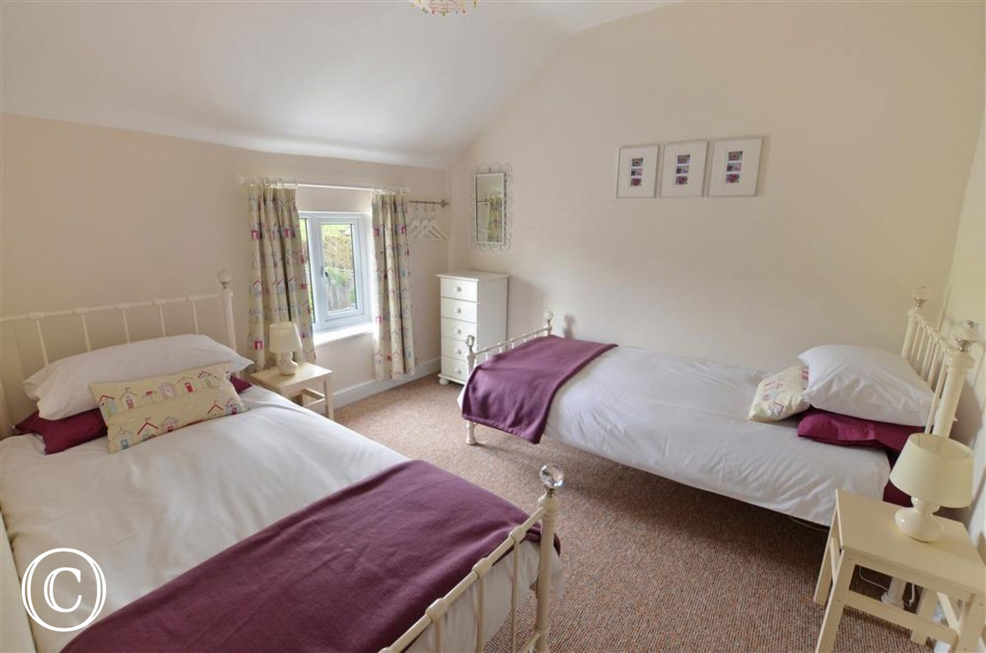 A twin room with lots of room and light, and soft furnishings with a beach hut theme.
