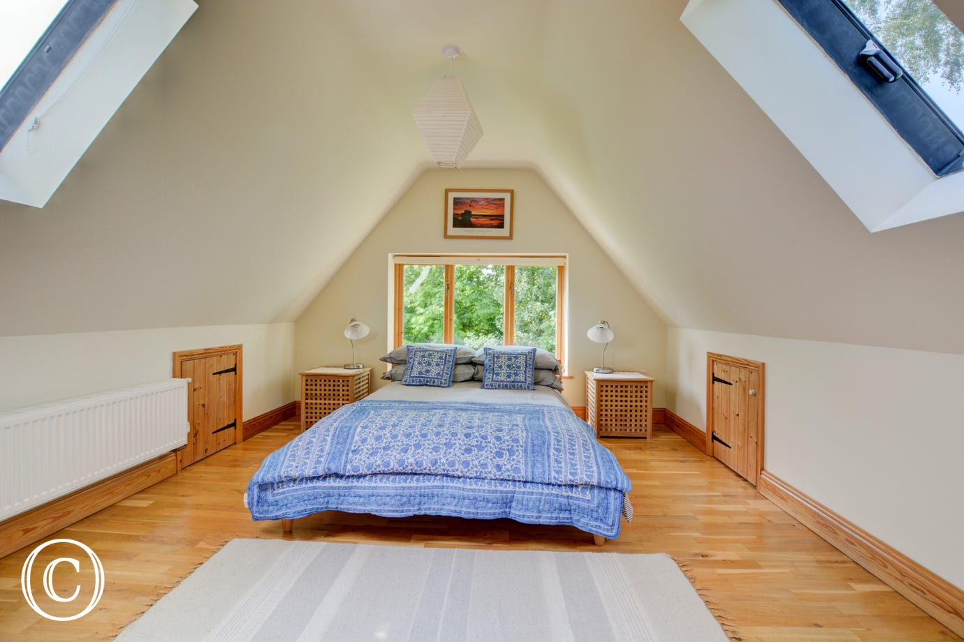 The double bedroom has sloping ceiling and a large picture window.