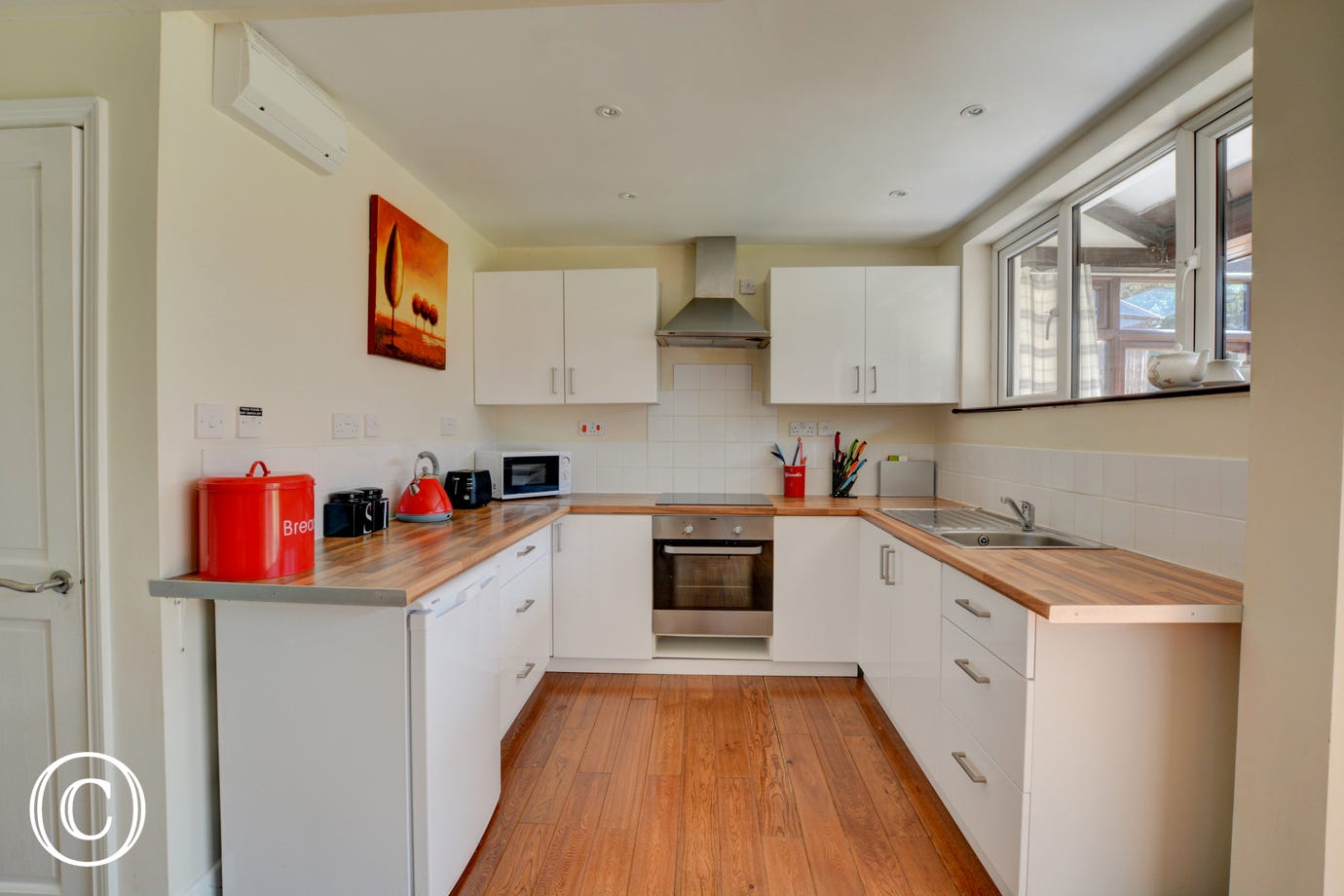 Fitted kitchen with electric double oven, electric hob, combination microwave and fridge