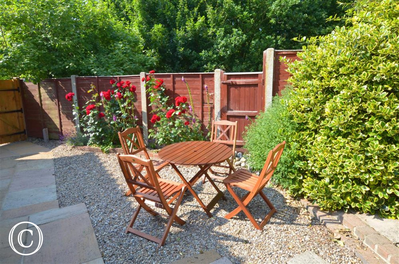 Enclosed gravelled outside area with table and chairs.