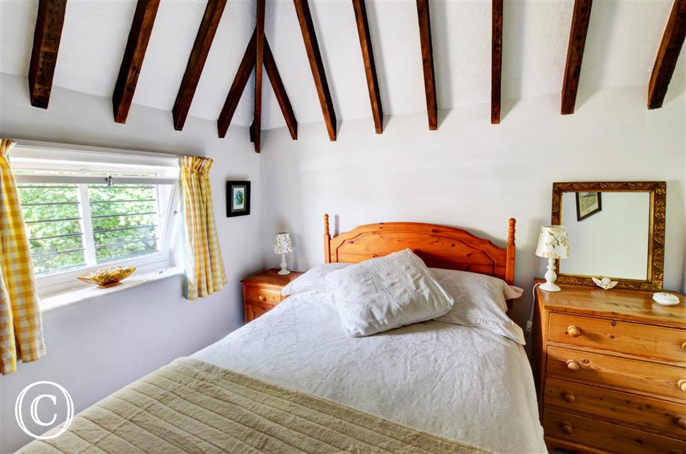 Bedroom one with a double bed and stunning open beams