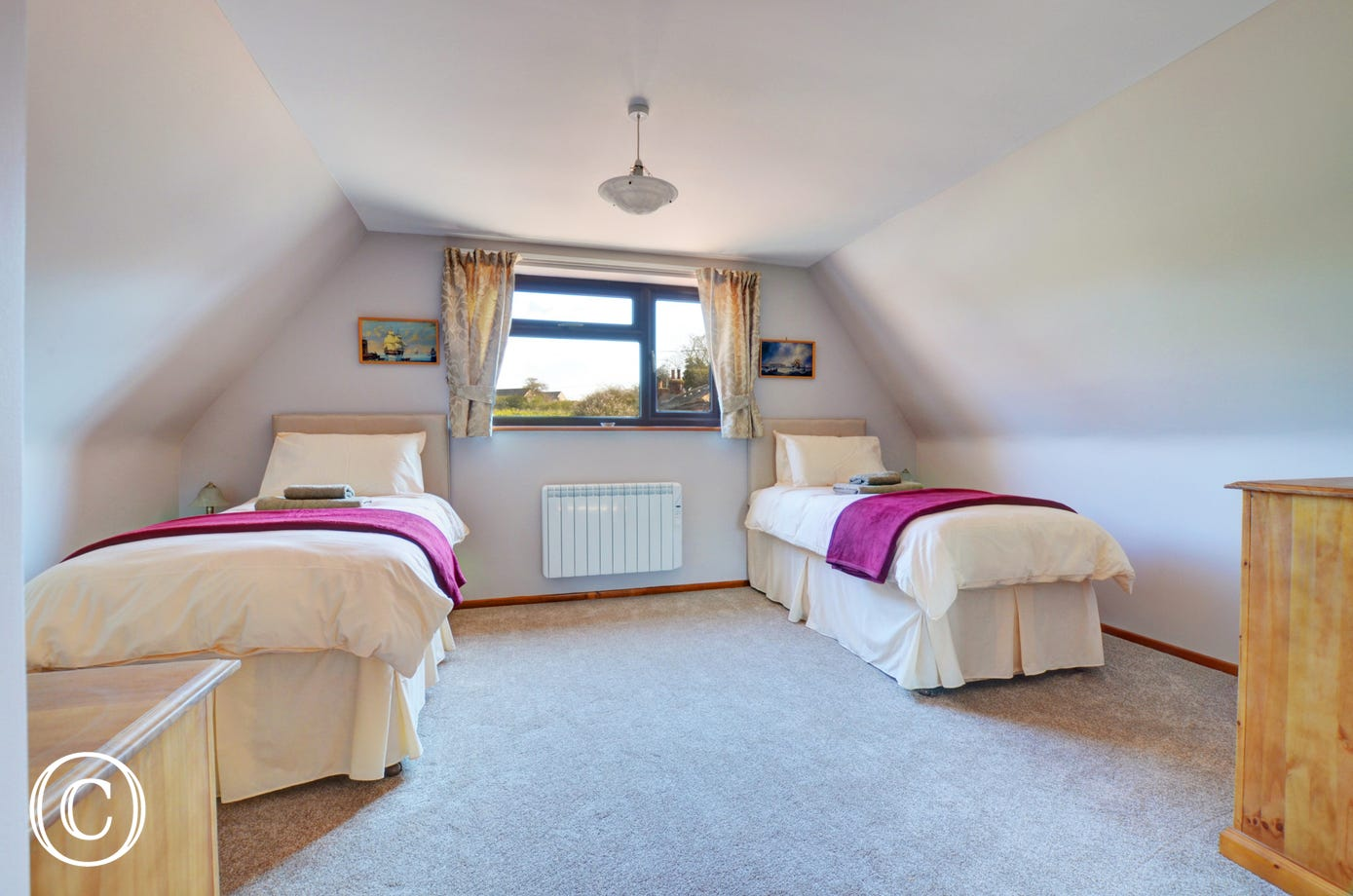 Twin beds within the third bedroom which is a light and airy room