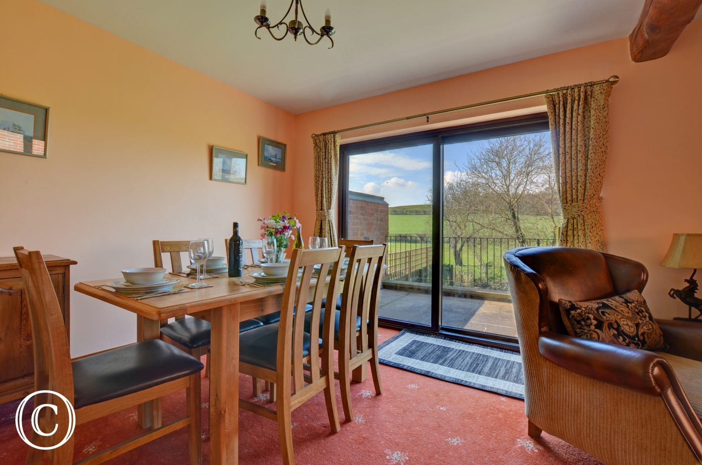 The dining area with a table and chairs has French doors leading to the raised patio area and lovely views