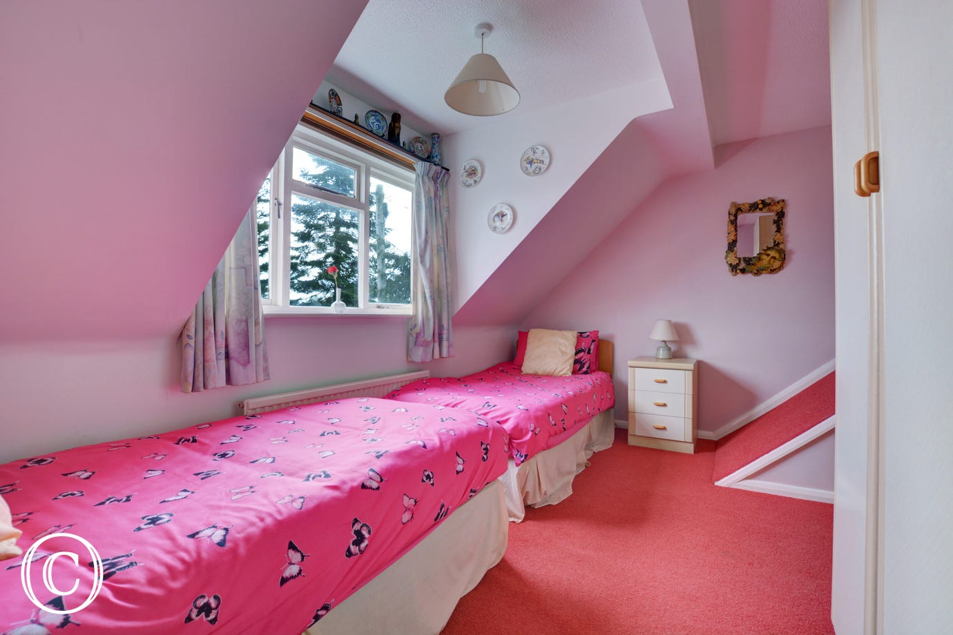 Twin bedroom with sloping ceilings and large window, ideal for children