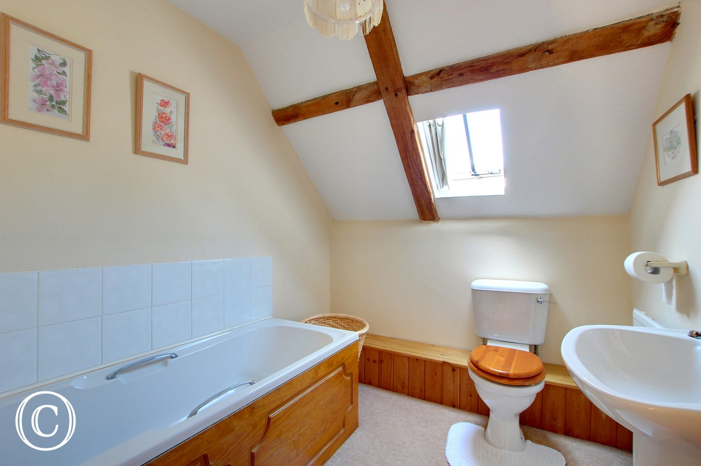 Bathroom with a bath and characterful beams