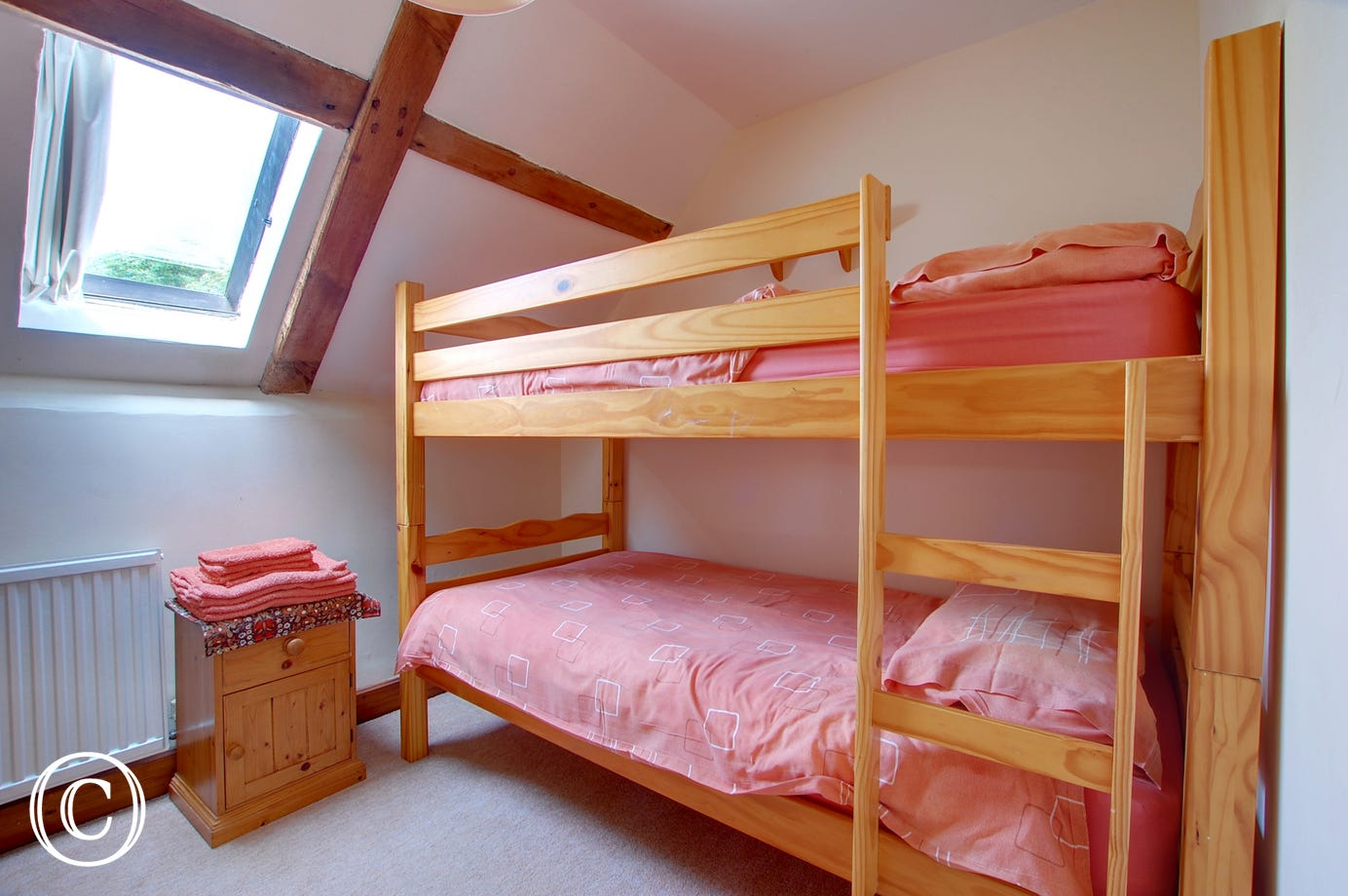 Light and airy bedroom with wooden bunk beds, ideal for children