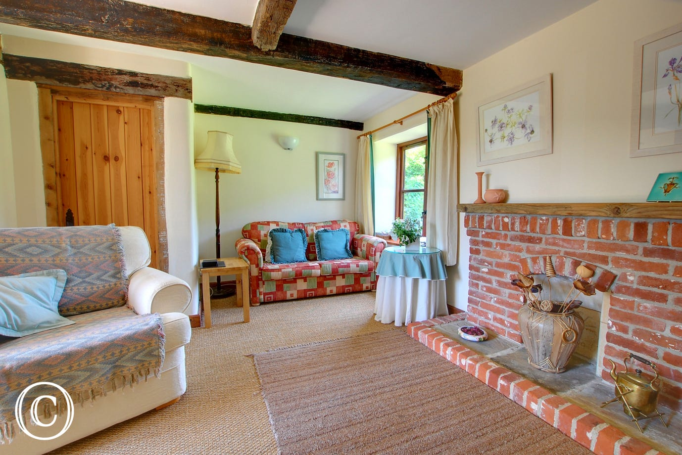 Spacious sitting room with beams and a feature fireplace for cosy evenings