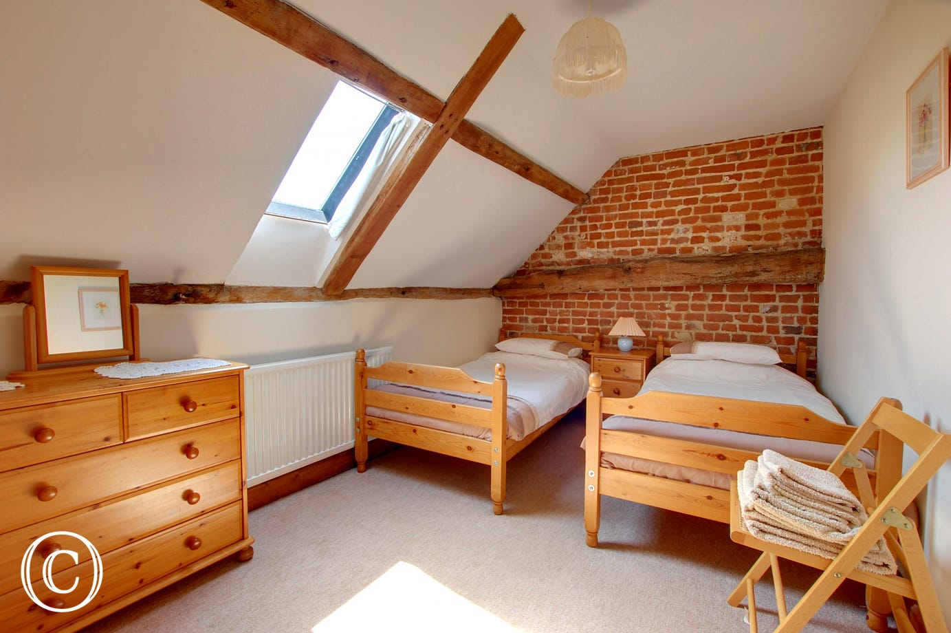 Bright twin bedroom with twin beds, sloping ceiling, exposed beams and exposed brickwork