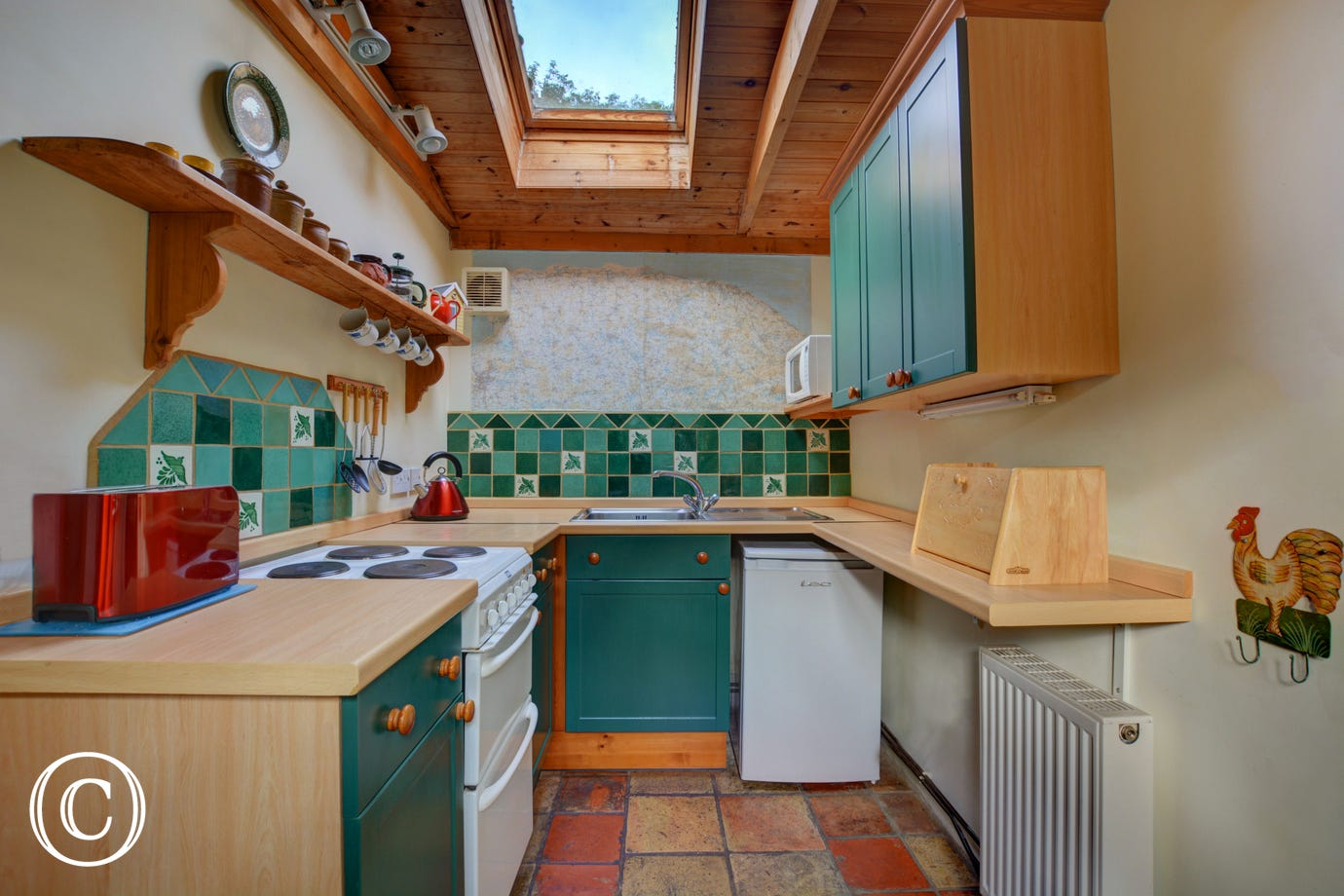 Compact kitchen with an electric cooker and other appliances and the added bonus of a cloakroom