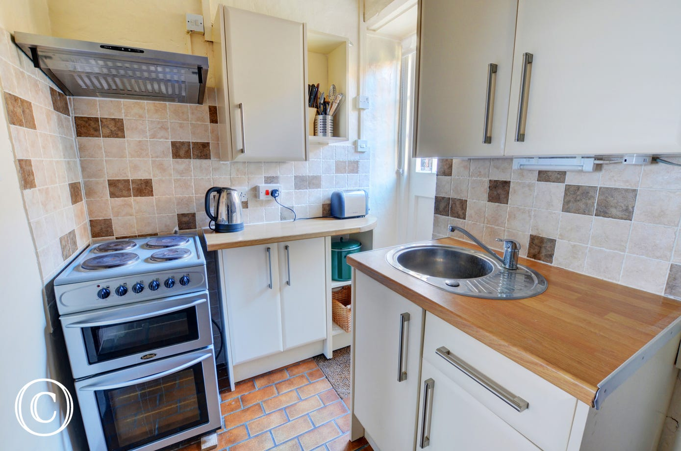 Compact kitchen with most major appliances and a door leading to the rear of the cottage