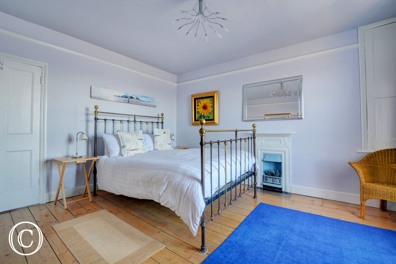 Bedroom 3 features a double iron bedstead and pretty fireplace and coastal art.