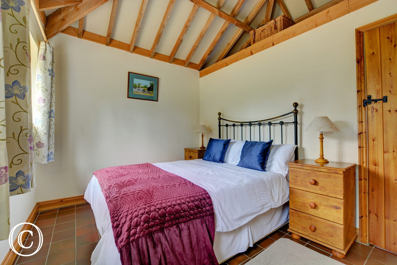 A double bedded room features an iron bedstead and pine furniture.