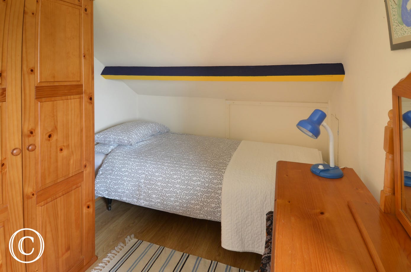 A single bed sharing a double bedded room.