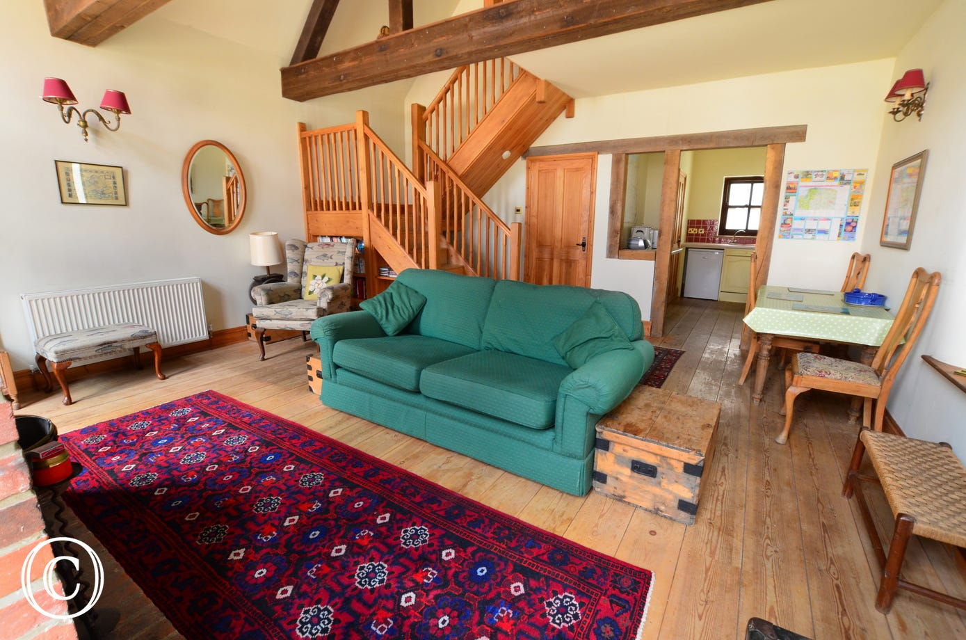 A pleasantly furnished, spacious sitting room with a vaulted ceiling and exposed beams