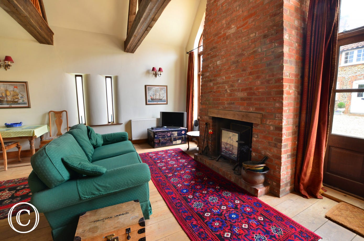 The sitting room has a wooden floor and there is a TV with Freeview and a  DVD player,