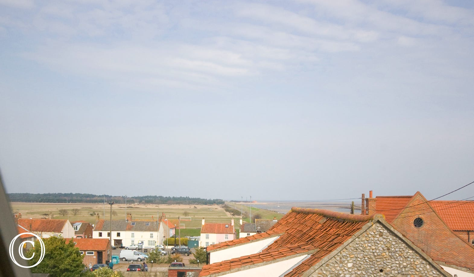 A view over the rooftops to the pinewoods and sea.