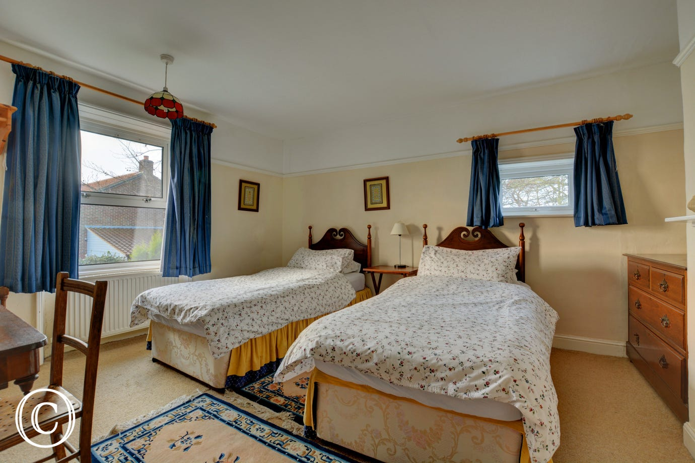 Traditionally furnished double bedroom with twin beds and a feature fireplace