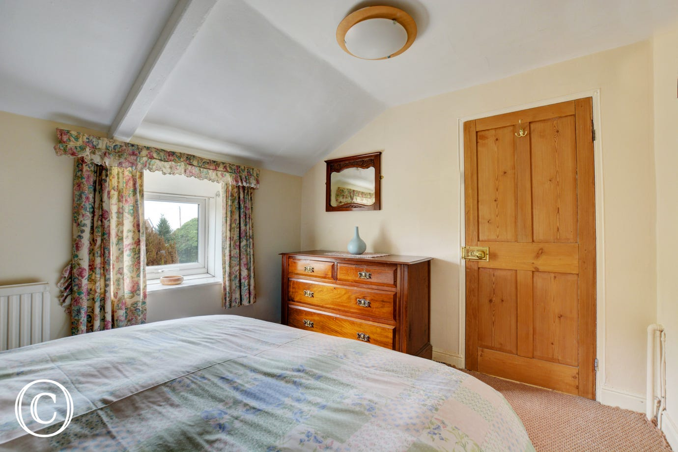 Bedroom three with double bed and chest of drawers.