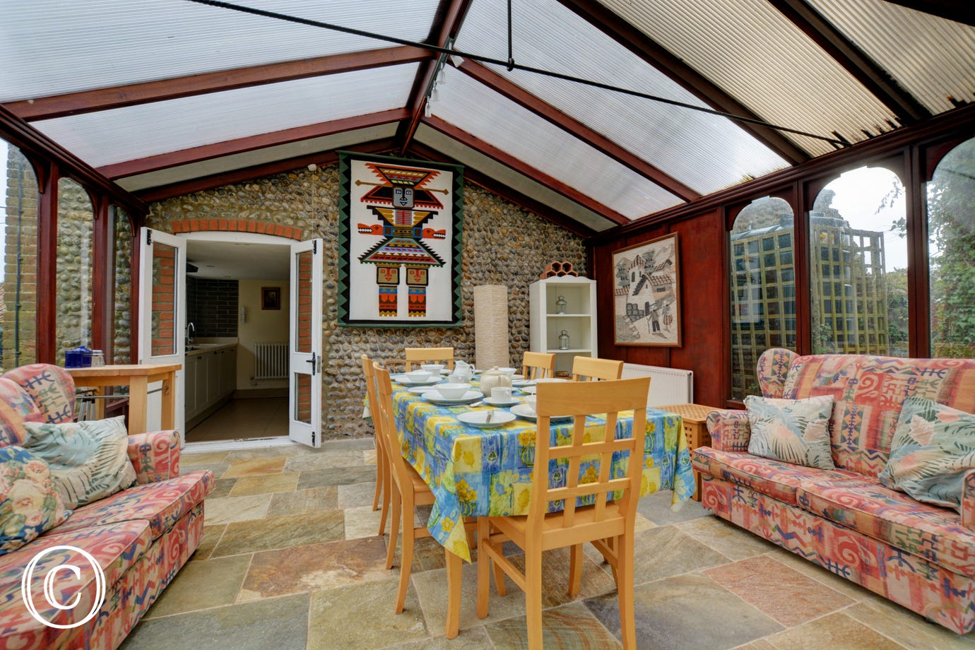 The conservatory is light and airy with a breakfast table,  chairs and comfortable seating