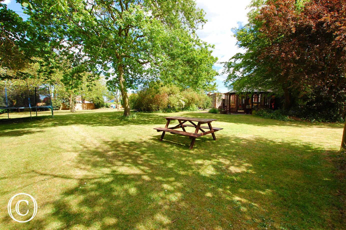 The garden is fully enclosed and has extensive lawned areas and established trees