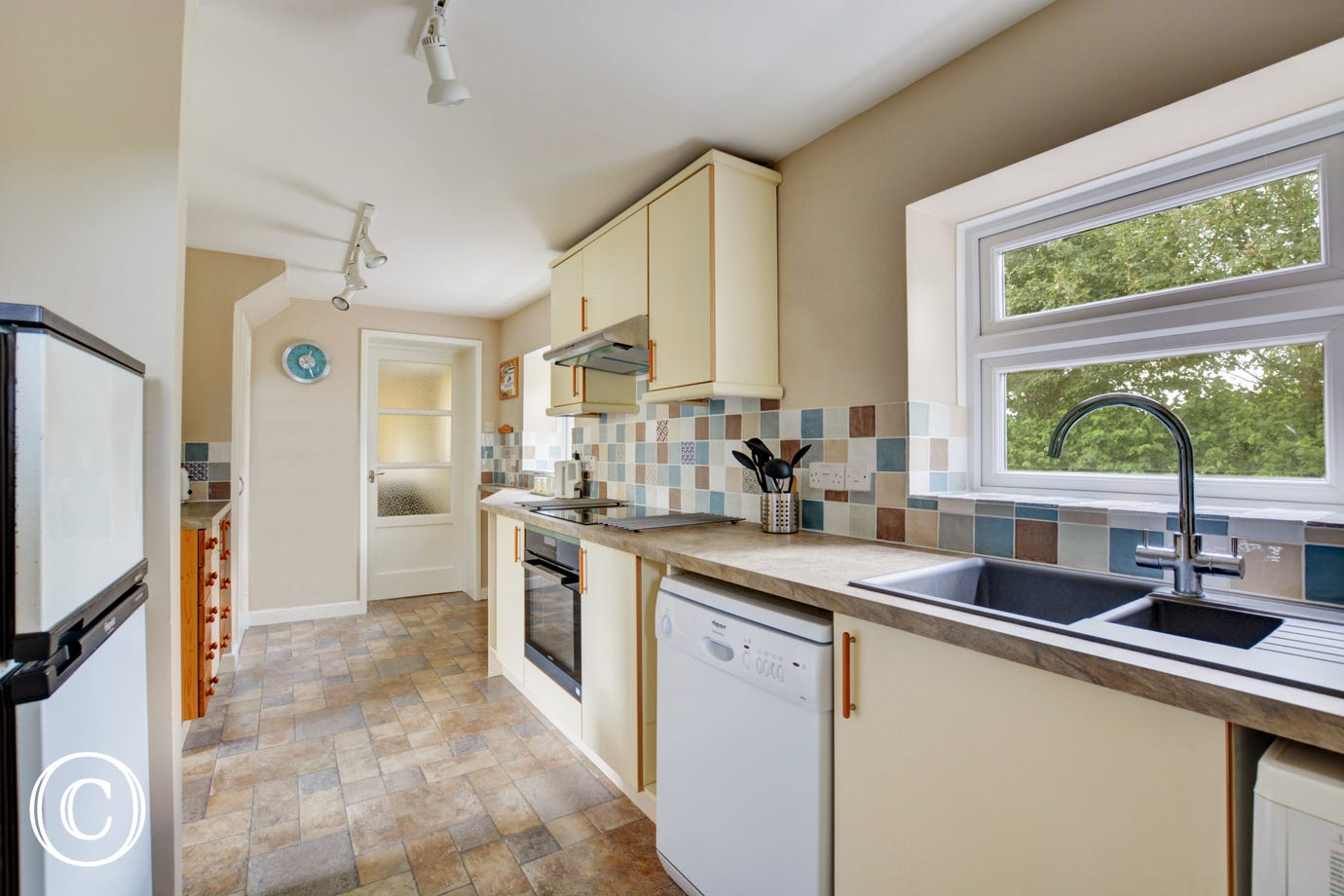 Bright and colourful kitchen with lots of storage and workspace and a downstairs cloakroom