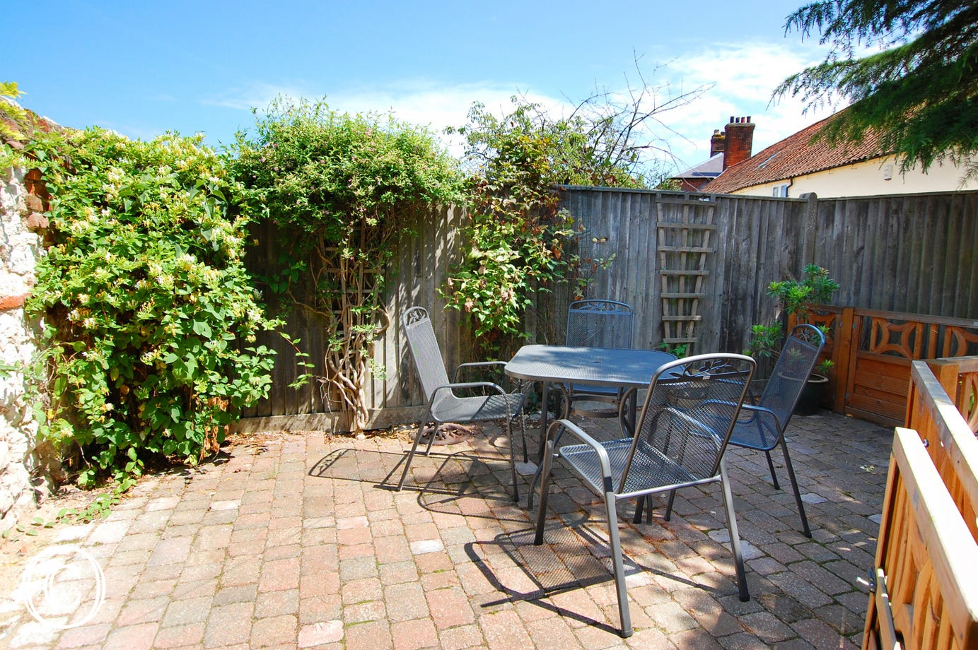 Enclosed private patio area with garden furniture, ideal for al fresco dining