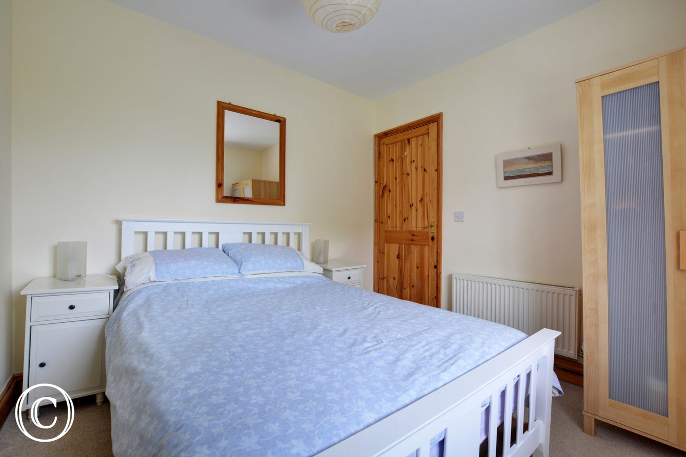 A traditional double bedroom with a double bed and pine bedroom furniture