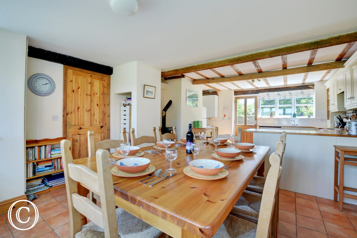 A lovely light and airy dining area with a table and chairs to seat 8, ideal for family meals