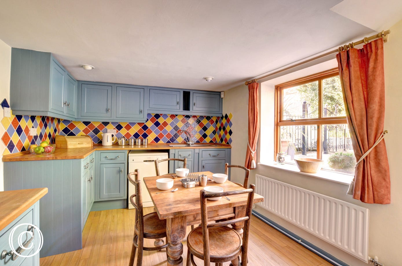 Colourful kitchen with table and four chairs