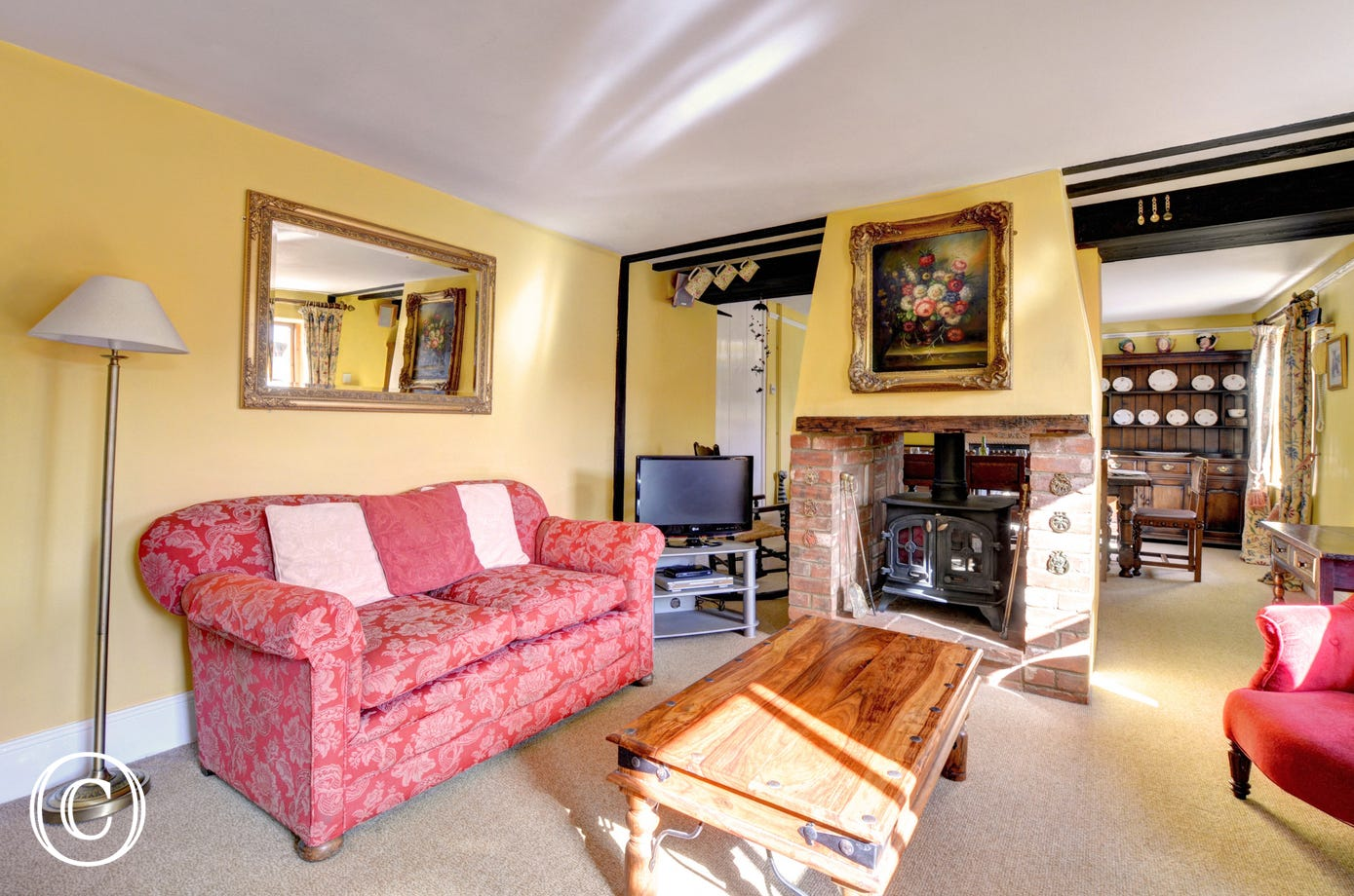 Spacious sitting room with comfy chairs and woodburner