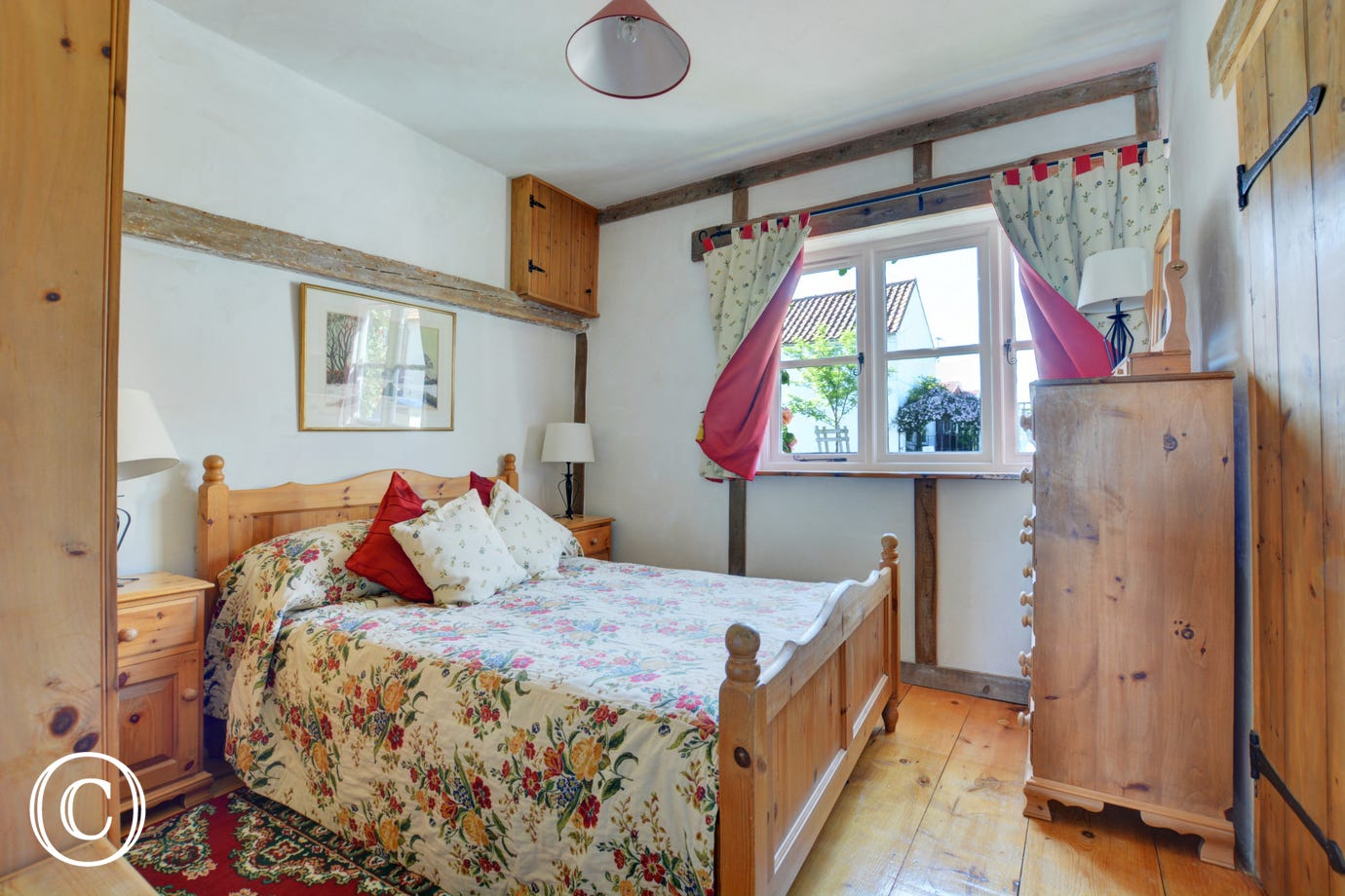 Lovely cottage style double bedroom with a double bed and pine furniture