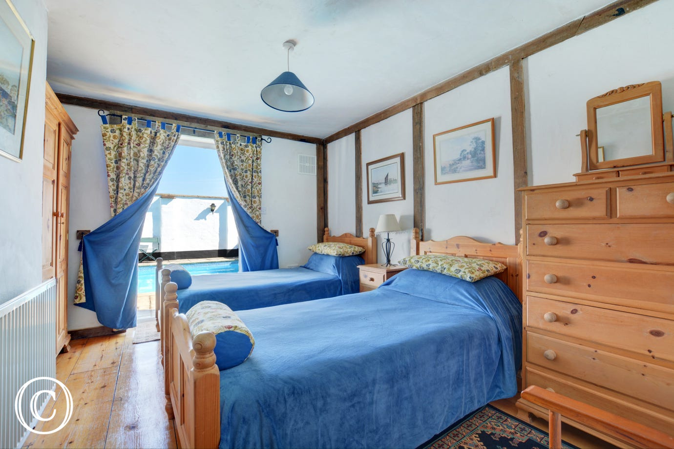 Traditional double bedroom with twin beds and patio doors leading to the swimming pool