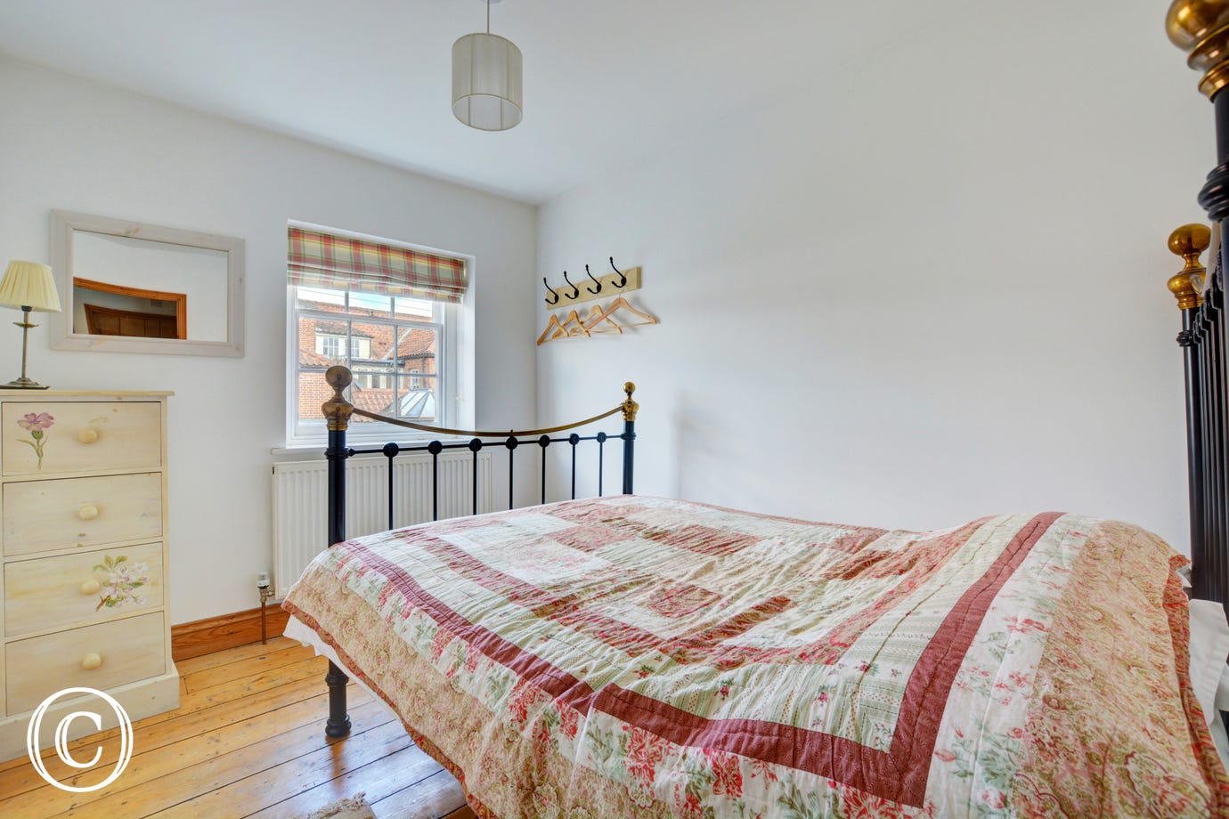 Compact but bright double bedroom with wrought iron double bed
