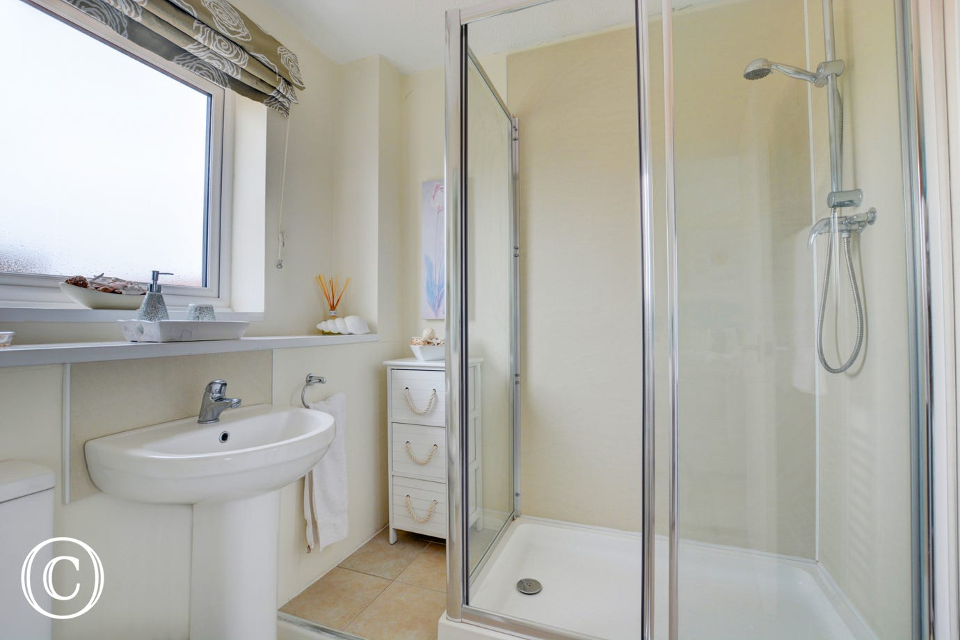 The en-suite shower room is bright and modern.  This view shows the bathroom cabinet and chrome towel rail, along with the wash basin and toilet.