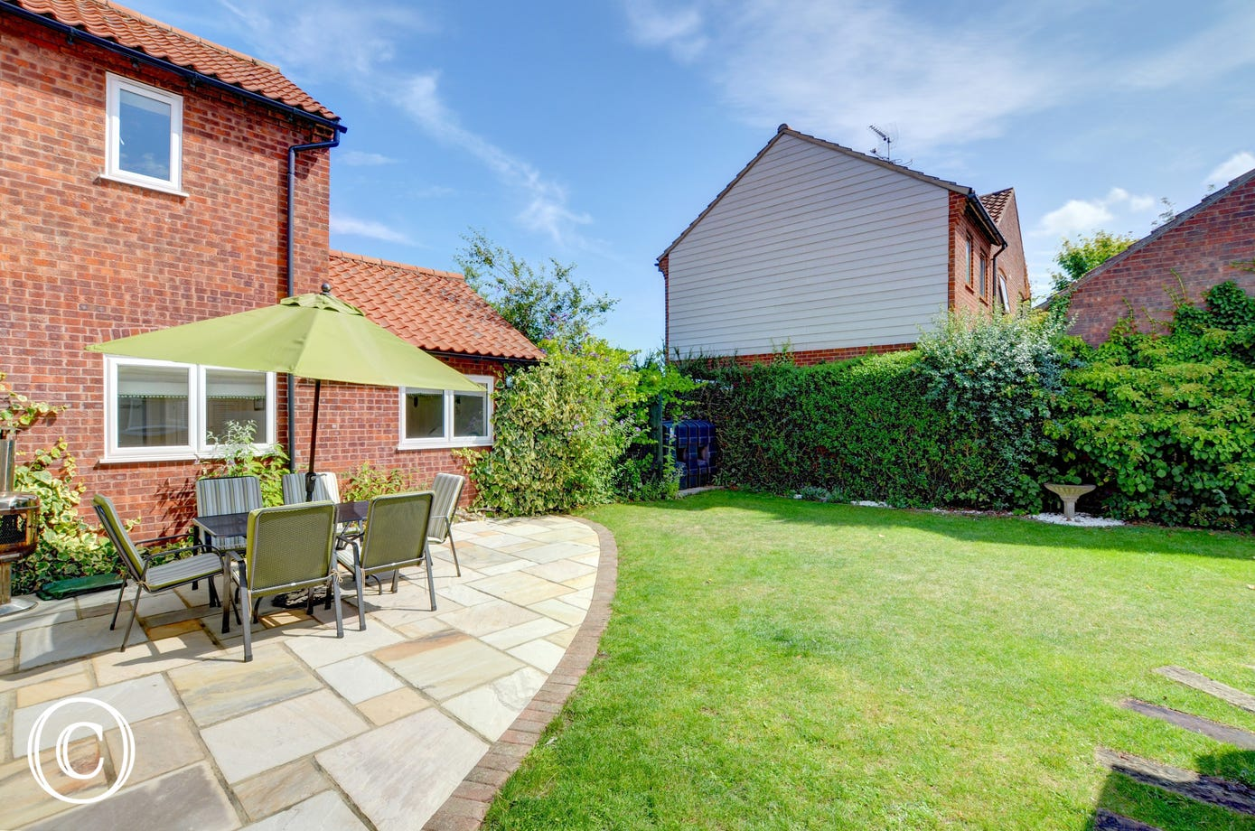 The fully enclosed garden has a patio area, with the rest laid to lawn.