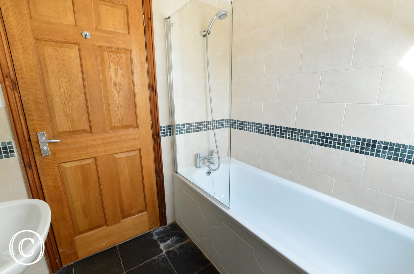 The family bathroom is on the first floor and is attractively tiled with a bath and an over bath shower