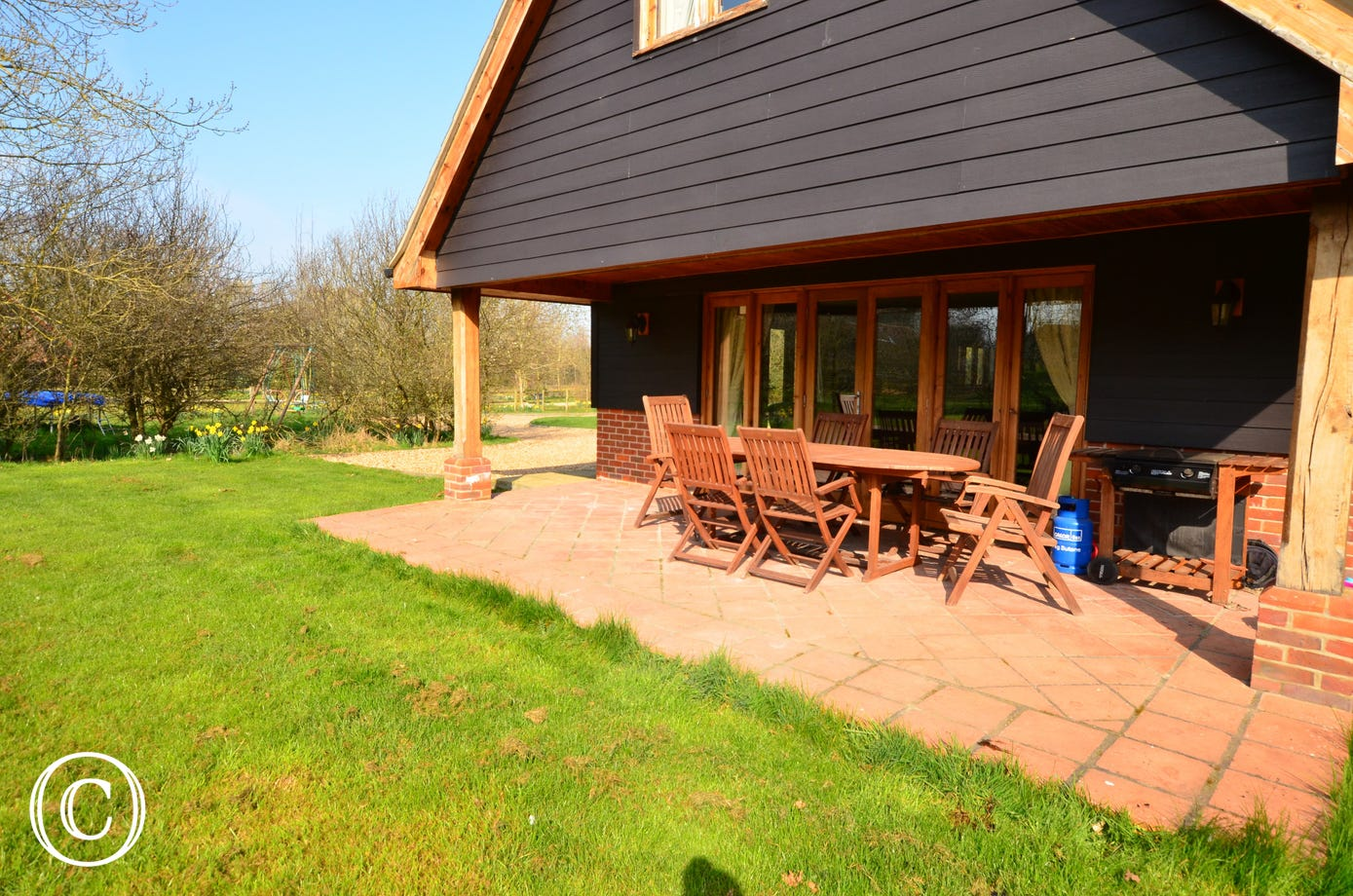 French doors from the sitting room open out onto the the large patio which is partially shaded by the overhang from the first floor. There is a large wooden table and chairs and a gas barbecue, this is an ideal space for relaxing family meals